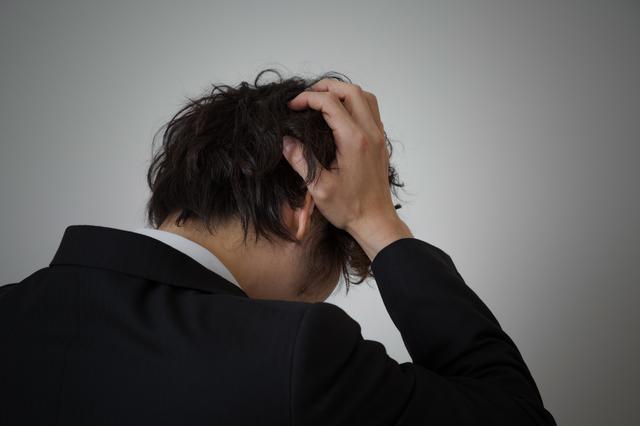 借金で頭を抱える男性