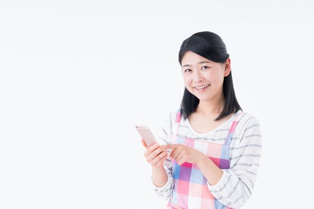 携帯電話を持った主婦の写真